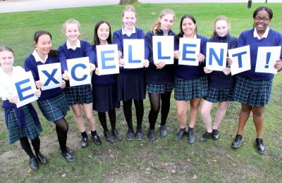 Girls holding excellent letters